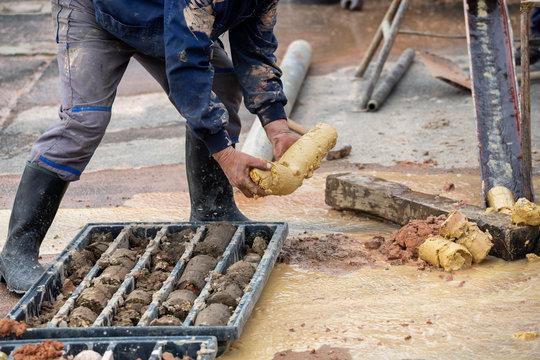 Driller obtaining soil samples in plastic core box