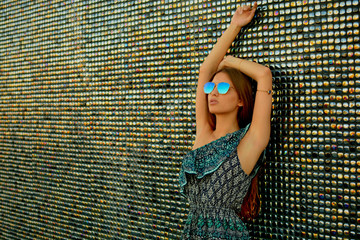 Young, beautiful and attractive Trendy cool hipster blond girl wearing a dress and sunglasses against a colorful wall of tiles Fotoväggar