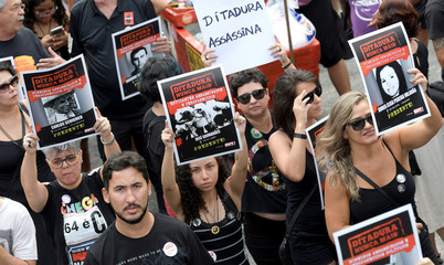 Demonstrators hold placards showing images of victims of dictatorship as they take part in a protest against celebrating the anniversary of a 1964 coup at the in Liberty Square or Praca da Liberdade in Belo Horizonte