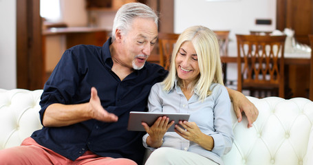 Portrait of a smiling mature couple using digital tablet on sofa at home