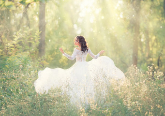 elegant and tender girl with black hair in white elegant light dress, lady runs in forest, turning pretty face on camera, her long train flying and fluttering in wind in bright rays of sunlight