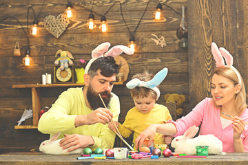Easter bunny costume. Mother, father painting Easter eggs.