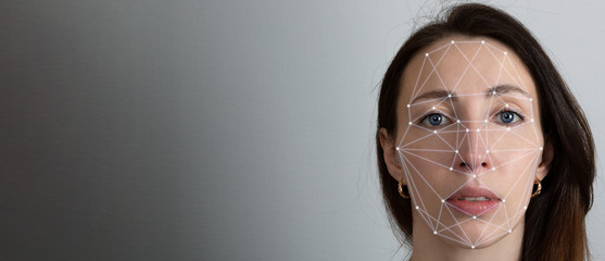 Facial recognition system, concept. Young woman on the grey background, face recognition