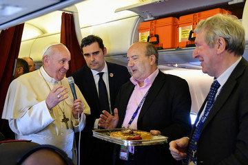 Pope Francis hands a cake to two reporters who both celebrated their birthdays while covering the Pope's trip, within addressing reporters aboard the plane bringing him back following a two-day trip to Morocco