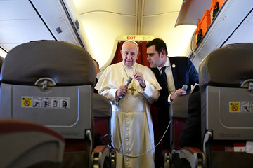 Pope Francis listens to interim director of Holy See Press Office, Alessandro Gisotti as he addresses reporters aboard the plane bringing him back following a two-day trip to Morocco