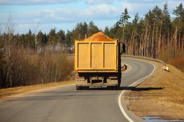 Transportation of building materials, heavy overloaded truck dump truck carries sand on a country road