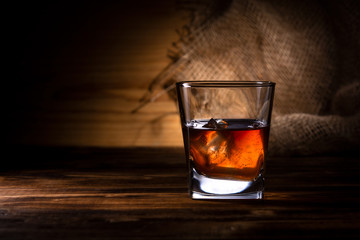 glass of whiskey or cognac on a wooden background