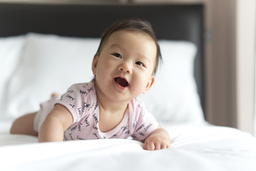 Young cute Asian baby crawling on bed in bedroom. The baby is smiling and looking at the right with happiness and joyfulness. Baby health care concept.