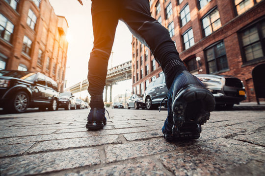 Man running at New York City street at sunset time. Men's feet with sport sneakers outdoors.
