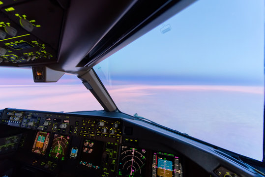 Beautiful twilight sunset sky at high altitude from airplane cockpit view. Inside cockpit can see flight instruments of airplane. Seen from first officer or copilot seat. Modern aviation concept.