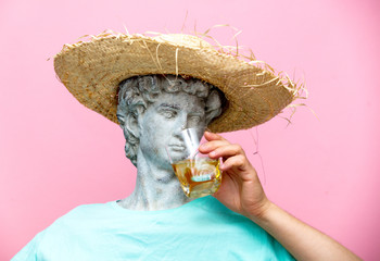 Antique bust of male in hat with whiskey glass
