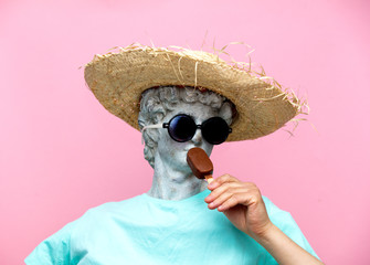 Antique bust of male in hat with ice-cream on pink background.