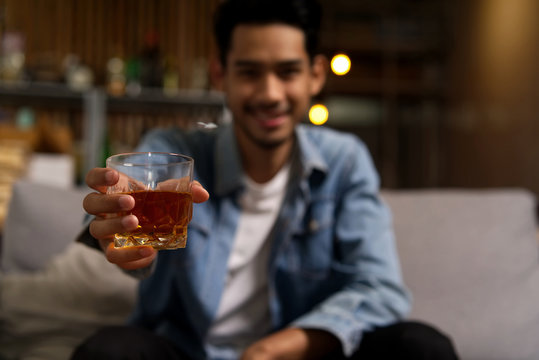 Close up shot of Asian man wearing jean jacket sitting on sofa holding glass of whiskey in night club restaurant. Focus on the glass. Alcohol drinking concept.