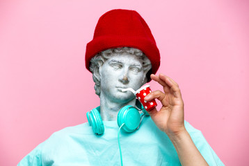 Antique bust of male in hat with cola drink on pink background