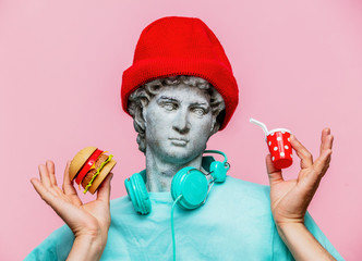 Antique bust of male in hat with cola drink and hamburger