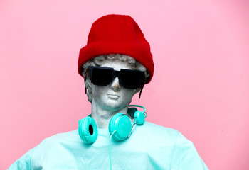 Antique bust of male in hat with headphones and sunglasses