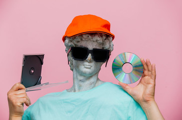Antique bust of male in cap with sunglasses and CD