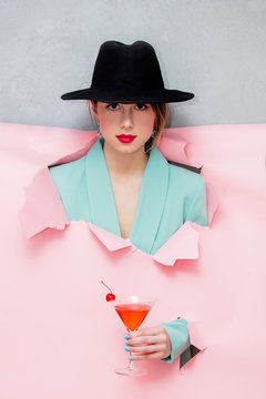 Beautiful woman in hat and blue classic jacket with martini glass