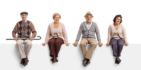 Two senior men and two senior women sitting on a white panel and posing