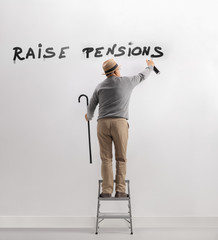 Senior man on a ladder writing graffiti on wall for raising pensions