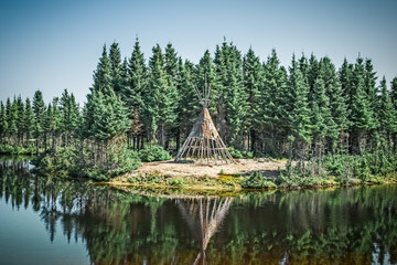 Native American tipi reflecting in the lake