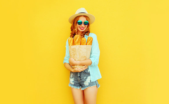 portrait happy smiling woman holding paper bag with long white bread baguette, wearing straw hat, shorts on colorful yellow background