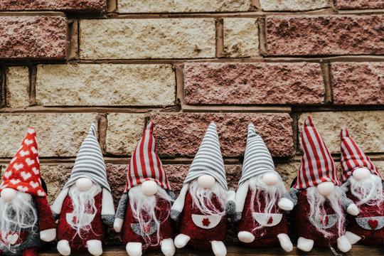 Seven gnomes, dwarfs seating against brick wall.