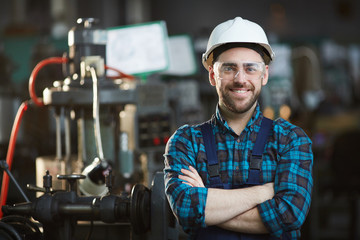 Waist up portrait of bearded factory worker wearing hardhat looking at camera while standing in workshop, copy space