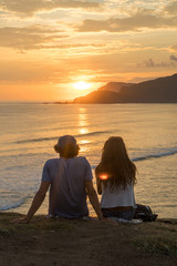 Young romantic couple on vacation sitting and watching colorful sunset over the sea coast.