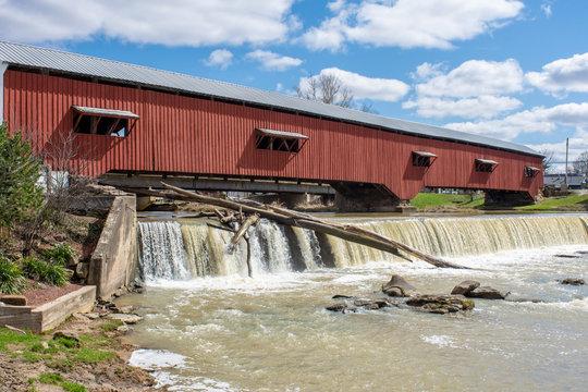A logjam is seen under a fall near a covered bridge in Bridgeton, Indiana