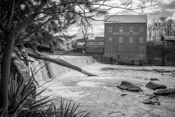 A Black and White photo Standing along the banks looking at the Bridgeton Grist Mill in Bridgeton, Indiana