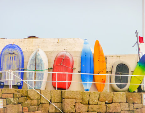 Fisher boat and surfboards lined up against a wall to dry