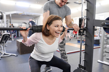 Middle-aged woman doing sports exercise in fitness center. Personal gym trainer assisting mature woman. Health fitness sport age concept Fototapete