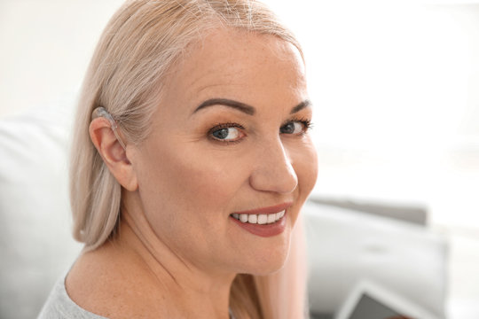 Mature woman with hearing aid at home