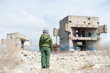 one little lonely child in green jacket standing on ruins of destroyed buildings in war zone