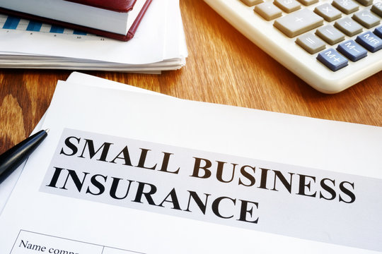 Small business insurance policy on a wooden desk.