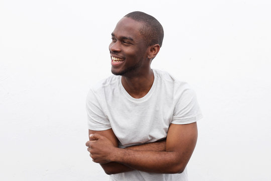 happy african american man laughing with arms crossed and looking away against white background