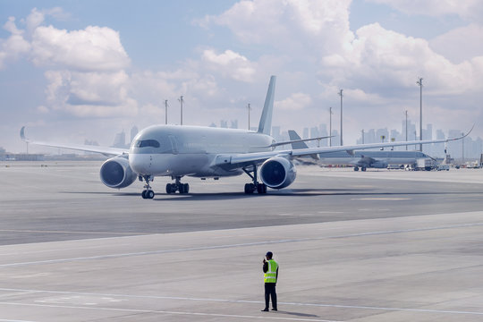Crew manage the movement of airplane at the airport. Aircraft is guided by ground staff to the parking place. Doha, Qatar.