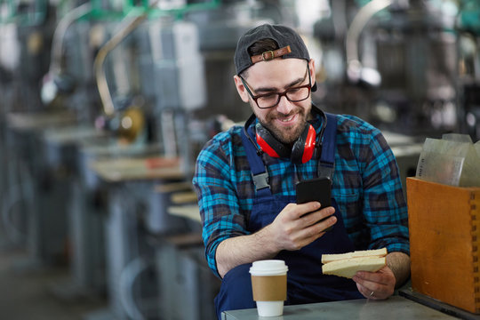 Portrait of smiling worker using smartphone during coffee break at factory, copy space