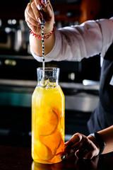 Barman prepares refreshing fresh fruit lemonade at a cafe