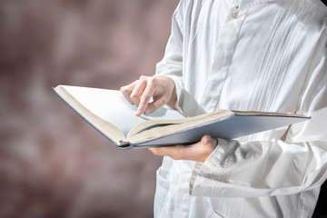 Muslim man standing while reading the quran on his hands
