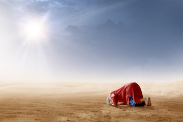 Rear view of asian muslim man praying in prostration position on desert