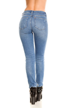 Pretty female legs and ass in jeans and boots on white background