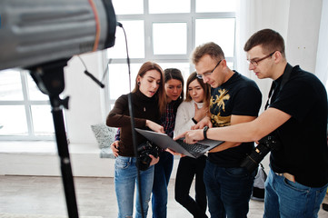 Photographer explaining about the shot to his team in the studio and looking on laptop. Talking to his assistants holding a camera during a photo shoot. Teamwork and brainstorm.