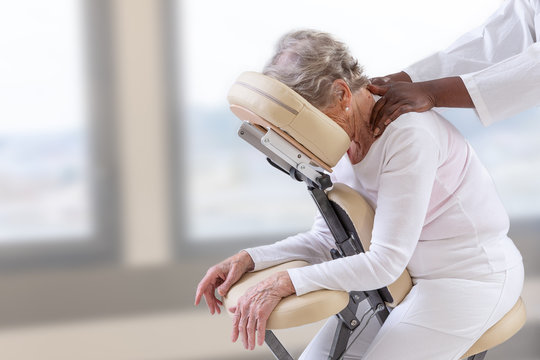 Senior woman getting massage in chair in therapy room