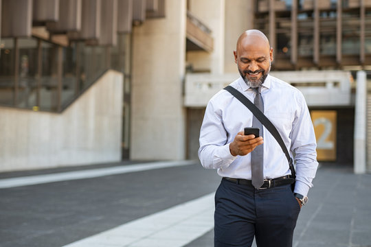 Satisfied businessman walking while using phone