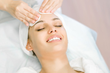 Fototapeta Cosmetologist hands cleanse the skin. Facial skin care. Smiling girl on a relaxing cosmetology procedure. Visiting cosmetology clinic. obraz