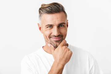 Image of optimistic man 30s with bristle wearing casual t-shirt smiling and touching chin