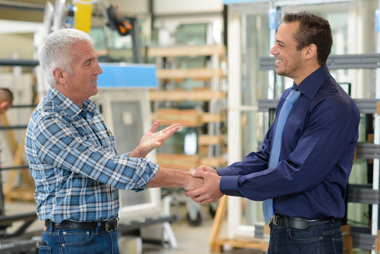 salesman and worker shaking hands in factory
