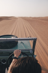 A man driving a vintage 4x4 car offroad in the desert on the sand dunes of Dubai